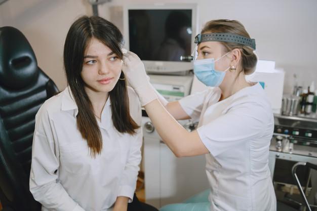 paciente-mujer-consultorio-medico-doctor-mascara-medica-lor-revisa-oidos-mujer_1157-45539
