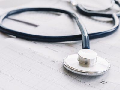 primer-plano-estetoscopio-carta-cardiograma_23-2147941821